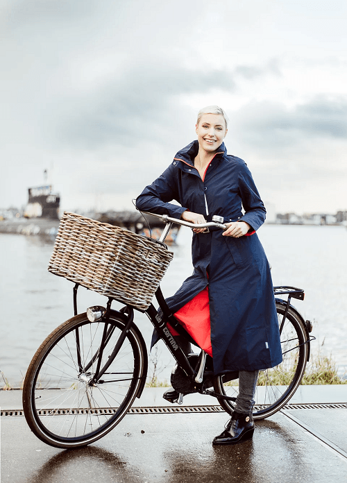 woman in long raincoat standing with bicycle